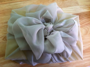 Curtain fabric gathered on all sides and tied into a bow.